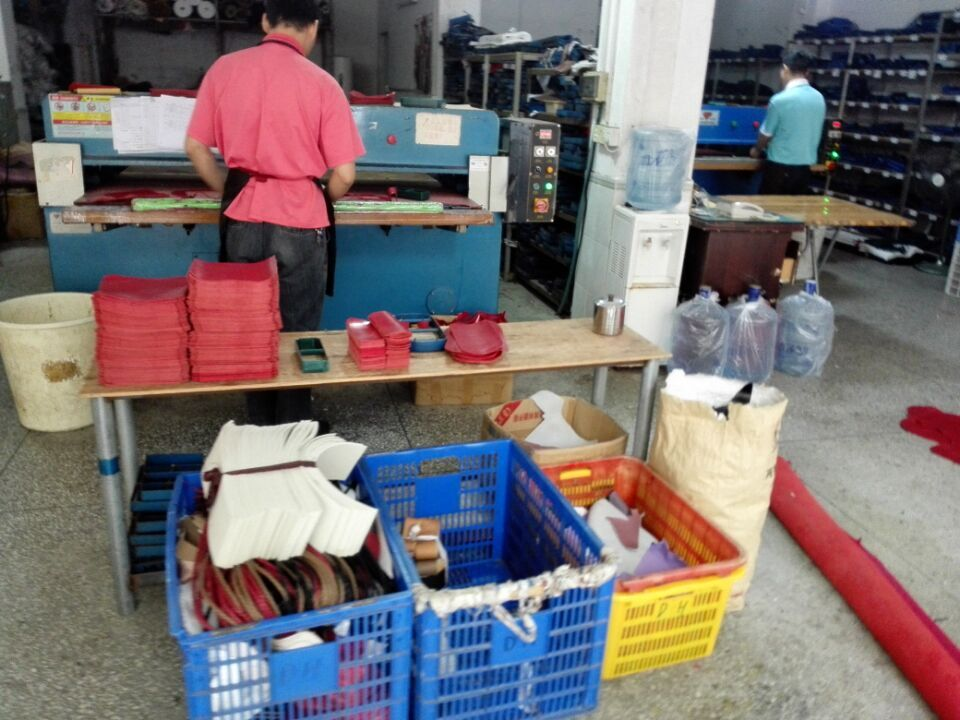 A worker is cutting different parts of the handbags in guangzhou handbag factory